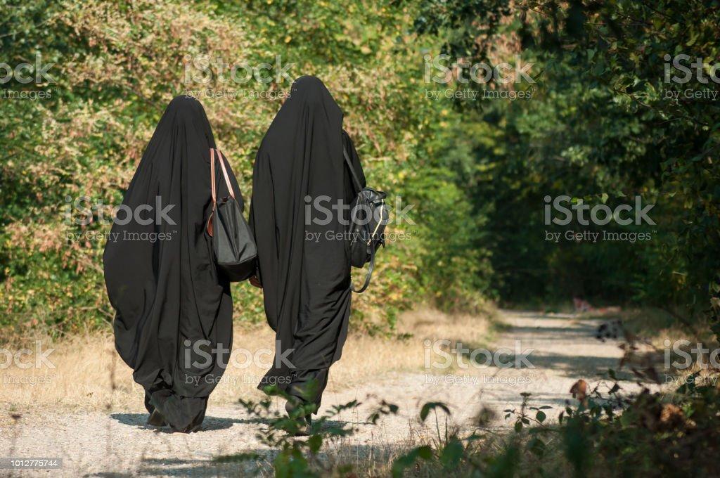 Frauen gehen in den Wald mit schwarzen Niqab auf Ansicht von hinten – Foto