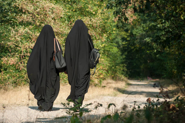 women walking in the forest with black niqab on back view portrait of two women walking in the forest with black niqab on back view religious celebration stock pictures, royalty-free photos & images
