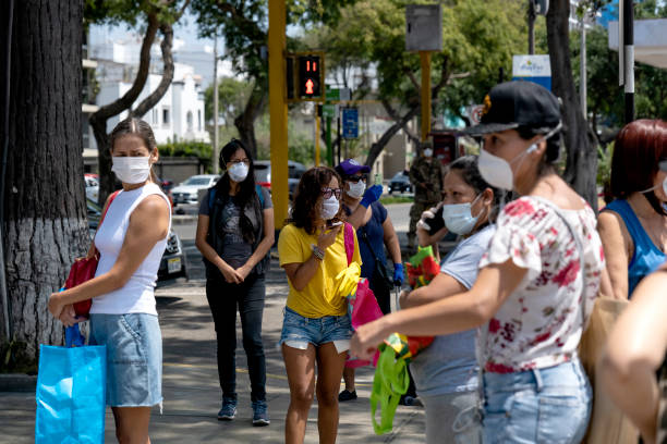 Women walking in the streets wearing a masks amid coronavirus outbreak Lima, Peru - April 4 2020: Women standing and walking in the streets wearing a masks amid coronavirus outbreak in south America. Only woman day, gender-based quarantine in COVID-19 times. amid stock pictures, royalty-free photos & images