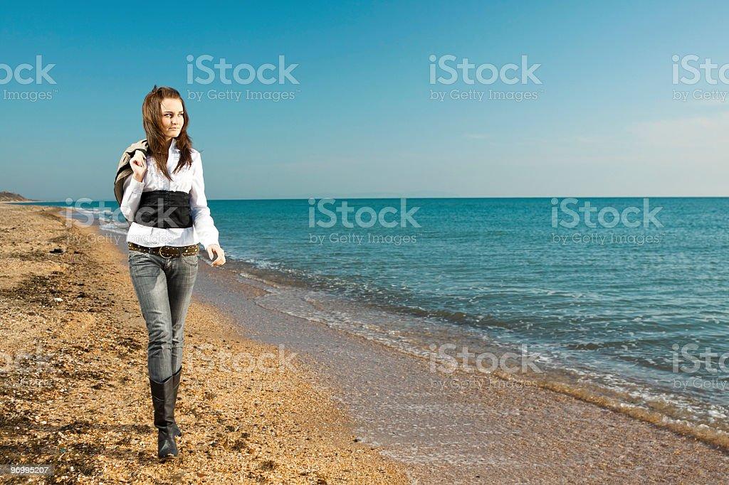 women walking on a sea coast stock photo