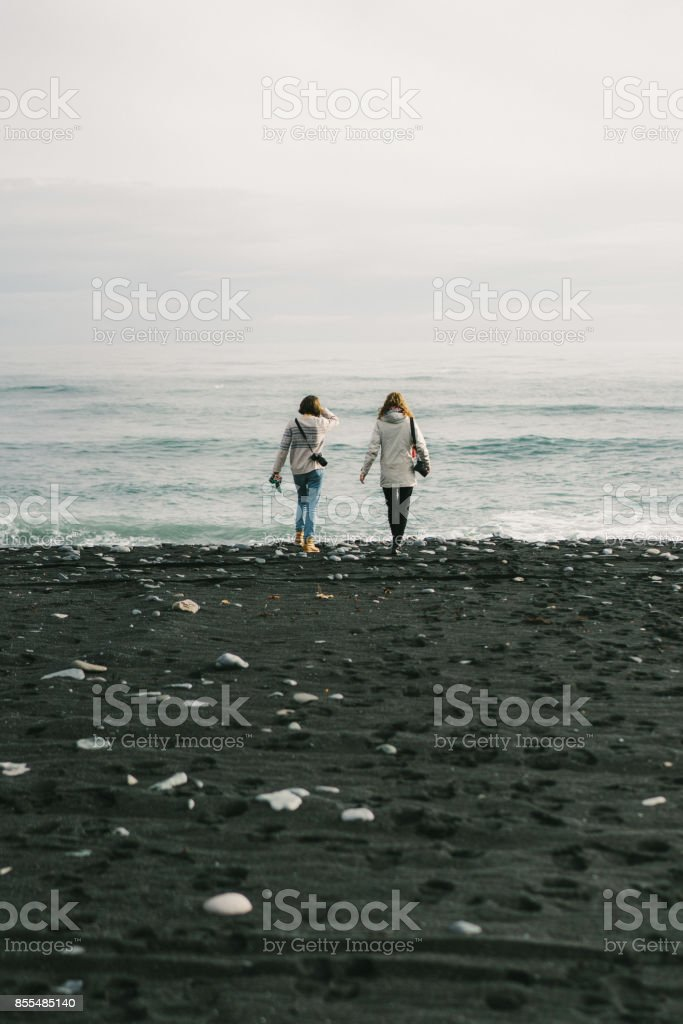 Women walking on the beach cover with icebergs  near the Jokulsarlon stock photo