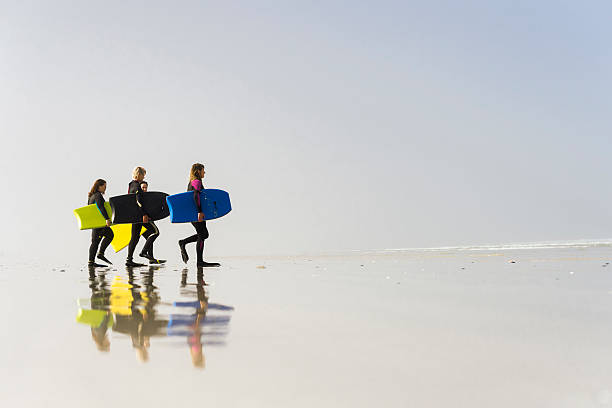 Women Walking On The Beach With Their Bodyboards stock photo