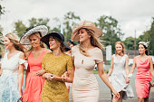 Young women walking towards the entrance for the horse race course.