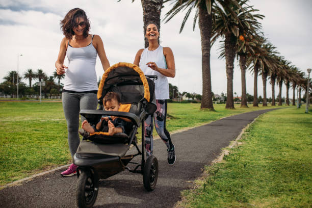 Women walking with baby in a stroller Two women walking with a baby pram in a park. Pregnant woman on a morning walk with her baby in a stroller. baby carriage stock pictures, royalty-free photos & images