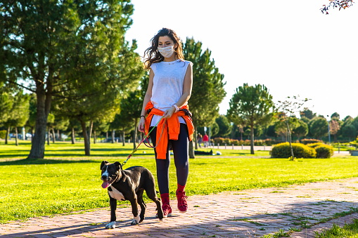 Woman With A Face Mask Walking Her Dog In Park.