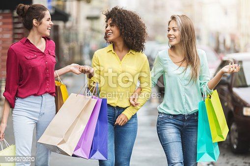 Happy women with colourful bags walking in the city after shopping