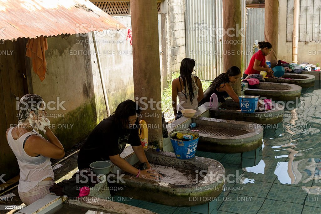 Women washing clothes in a laundry stock photo