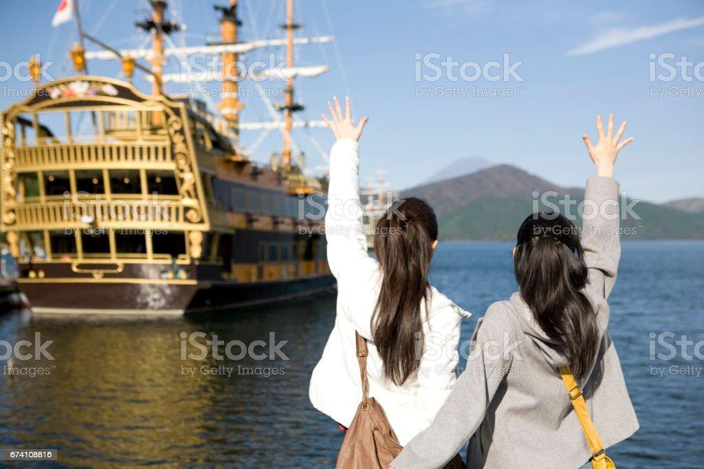 Women waving to the ship royalty-free stock photo