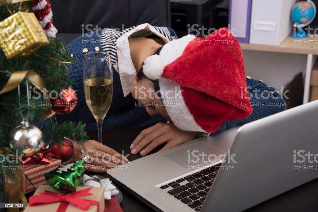 Frauen tragen Hut Santa schlafen auf ihrem Schreibtisch nach Weihnachten zu feiern, im Büro. – Foto