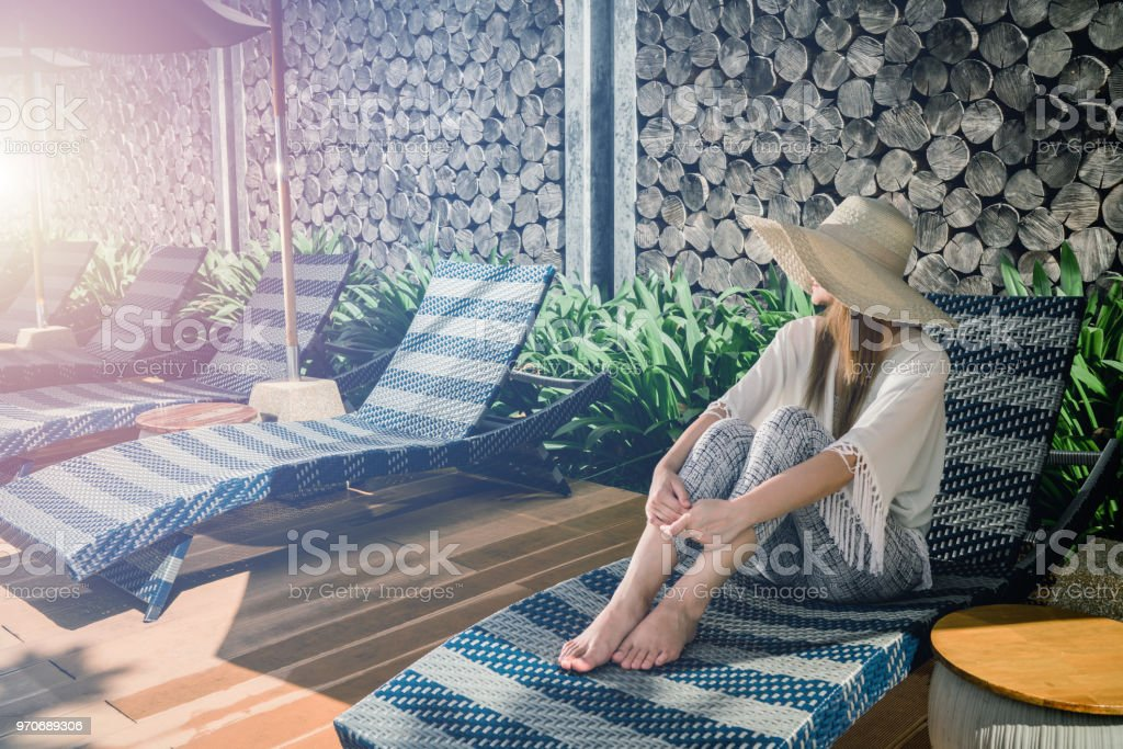 Women wear hat Sitting on comfortable chair in pool villa sea view, cloud and blue sky is endless background, copy space. Women wear hat Sitting on comfortable chair in pool villa sea view, cloud and blue sky is endless background, copy space. Adult Stock Photo