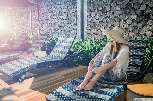 Women Wear Hat Sitting On Comfortable Chair In Pool Villa Sea View Cloud And Blue Sky Is Endless Background Copy Space Stock Photo - Download Image Now