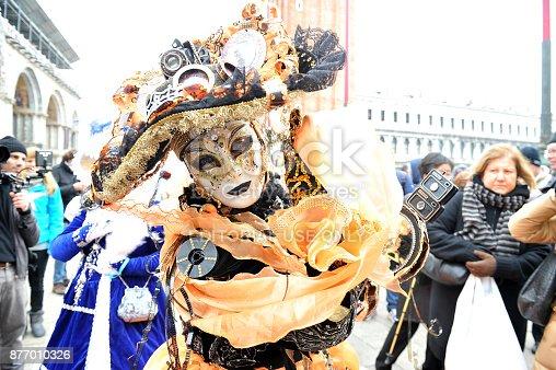 istock Women wear orange costume in Carnival of Venice, Italy. February 12, 2013 877010326