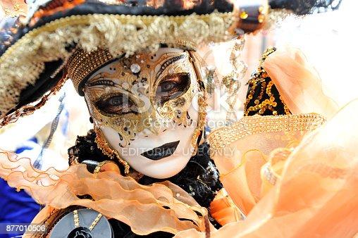 istock Women wear orange costume in Carnival of Venice, Italy. February 12, 2013 877010506
