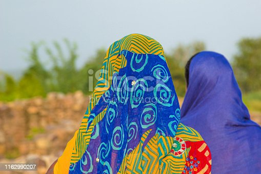 women wear the colorful headscarfs with traditional pattern in the heat of india but without covering the face