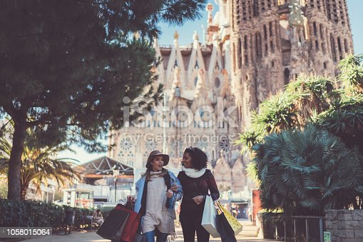 istock Women wearing a paper bags after shopping in Barcelona 1058015064