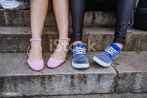 Two young women wearing dress shoes and sneakers and sitting next to each other on stairs. Close up view.