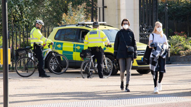 Women wearing masks, police officers on bikes and ambulance on Pall Mall during coronavirus crisis London, UK - April 4th 2020:  Girls crossing the street wearing masks with police officers on cycles talking with ambulance staff near James' Park in central London during lockdown central london stock pictures, royalty-free photos & images