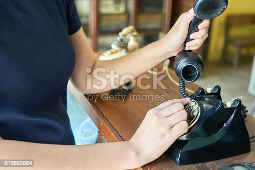 Women wearing navy dresses are picking up old phones. Hand holding telephone and dialing a number. Retro telephone concept
