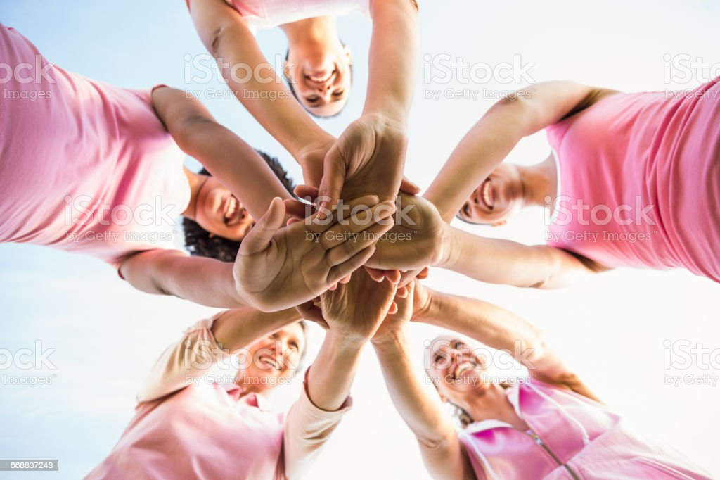 Women wearing pink for breast cancer and putting hands together stock photo