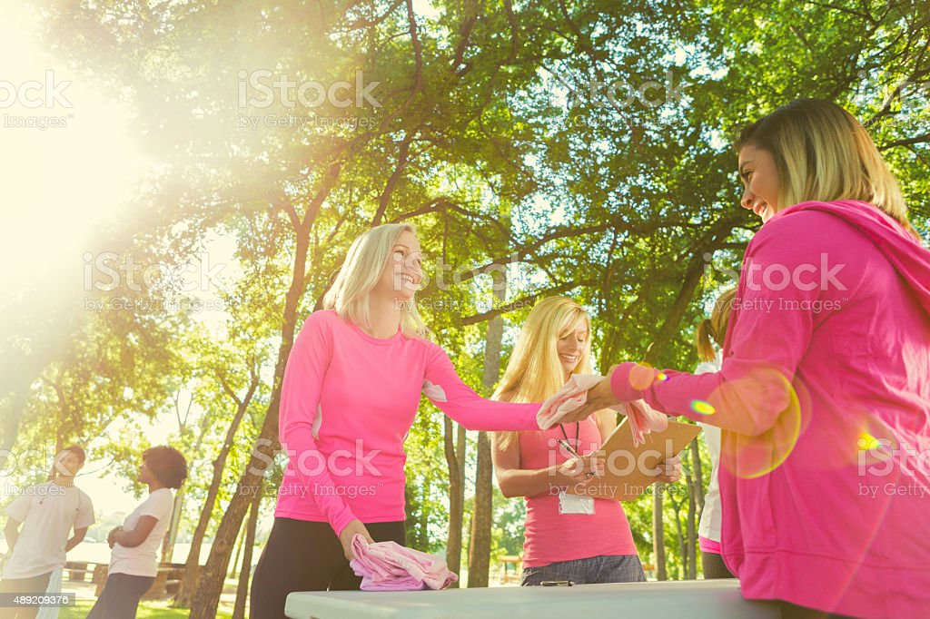 Women wearing pink, signing up for breast cancer charity race stock photo