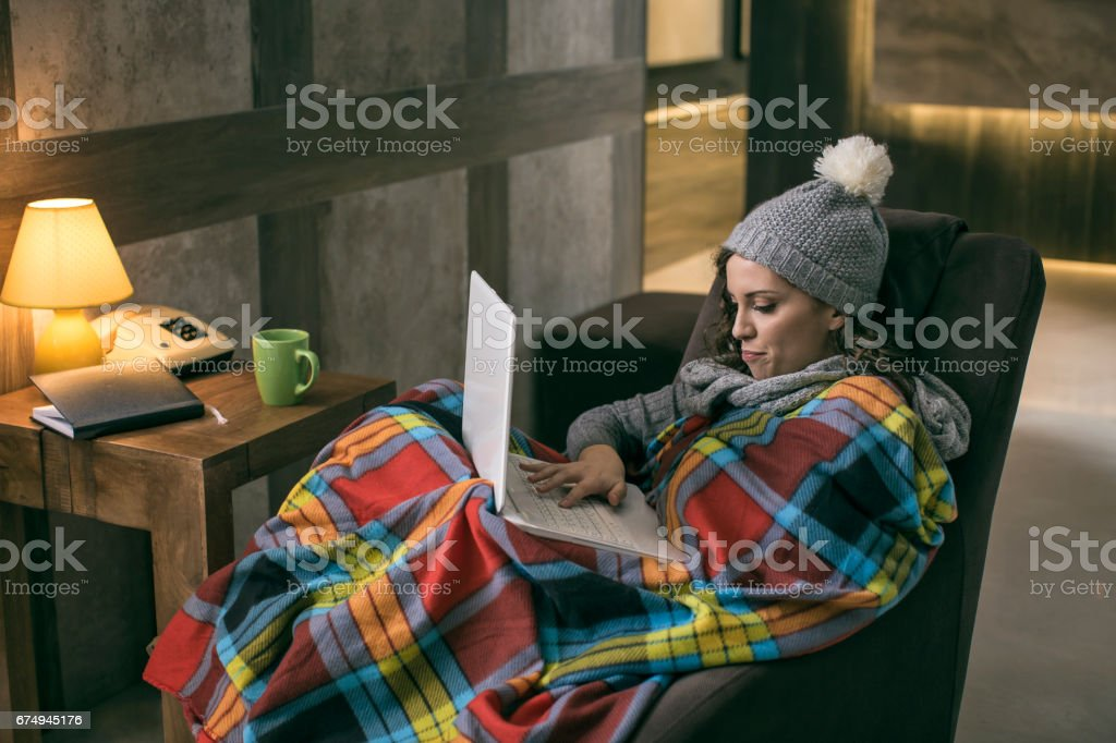Women wearing winter cap working on laptop wrapped in a blanket at home with no heating stock photo