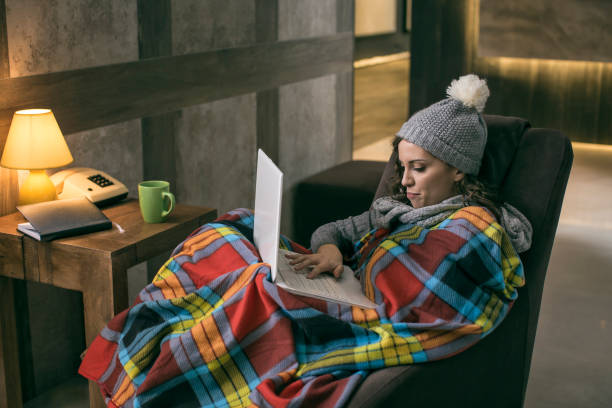 Women wearing winter cap working on laptop wrapped in a blanket at home with no heating Young women wearing winter cap working on laptop wrapped in a blanket at home with no heating warm clothing stock pictures, royalty-free photos & images