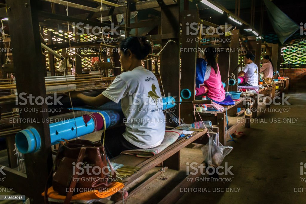 Women weave patterns with silk in Cambodia stock photo