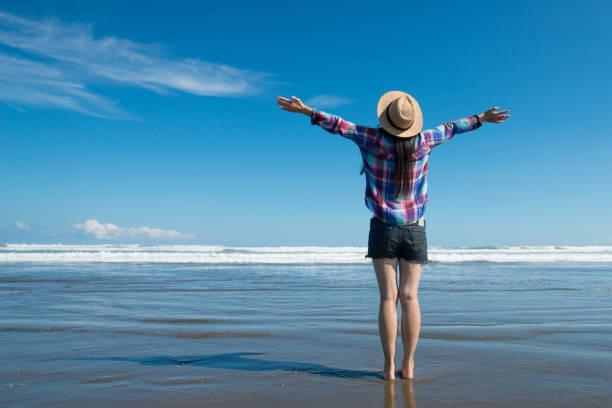 在海灘上舉起雙手的女人 - 恢復精神 個照片及圖片檔