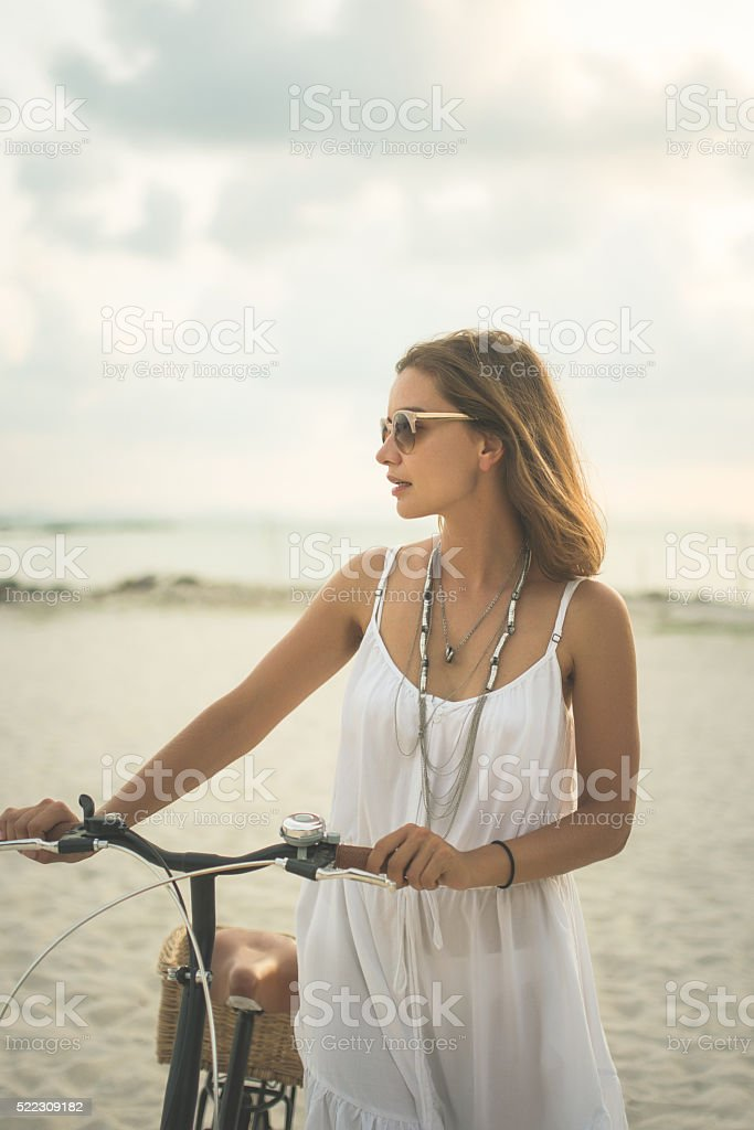 Women with a bicycle walking on the beach stock photo