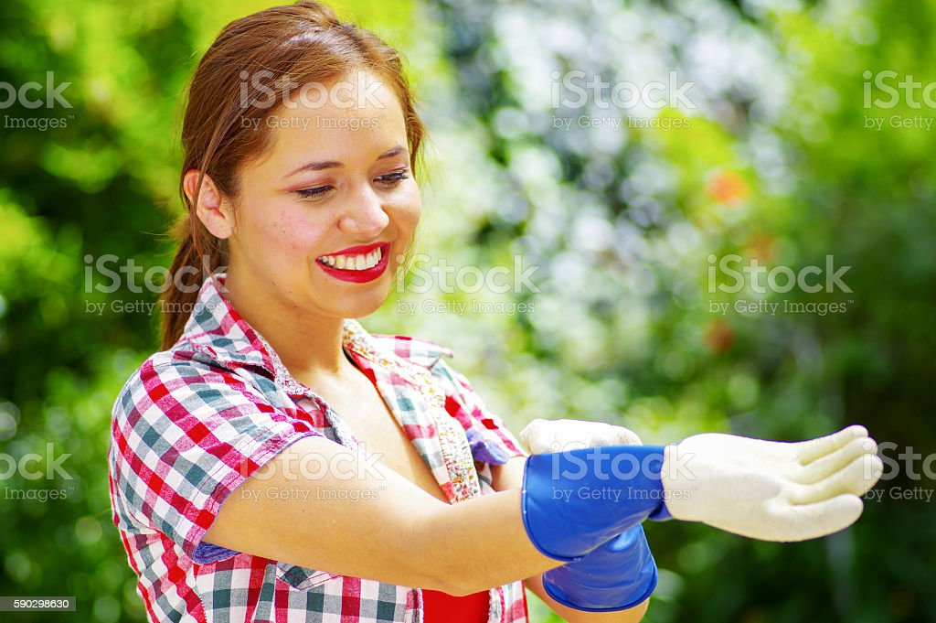women with a colorfull shirt putting on gloves royaltyfri bildbanksbilder