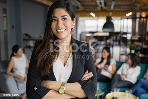 Portrait of women standing in office with coworkers in background.
