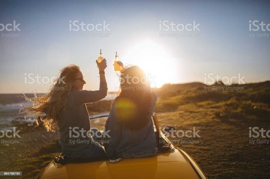 Women with cabriolet car relaxing and drinking soda at beach royalty-free stock photo