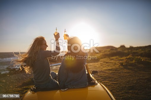 Women with vintage convertible car relaxing and toasting with drinks at the beach at sunset