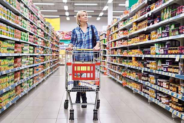 Women with cart shopping in supermarket Women housewife with cart shopping in supermarket grocery aisle stock pictures, royalty-free photos & images