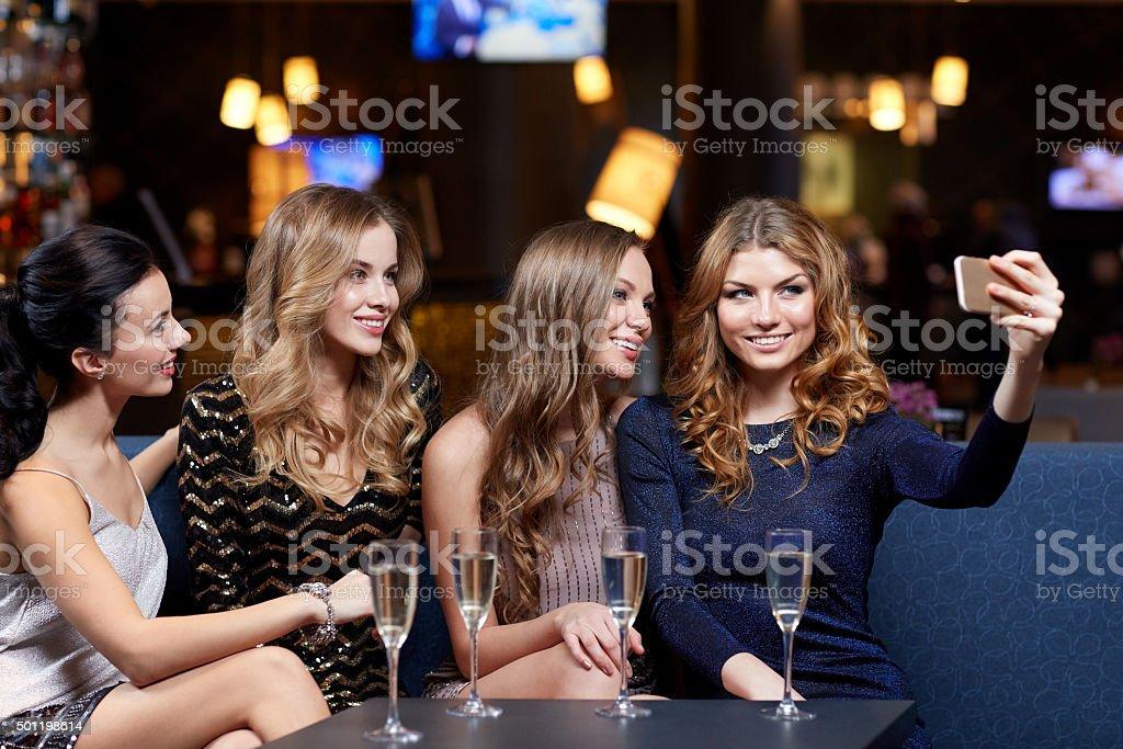 Femme avec champagne prenant selfie au night-club - Photo