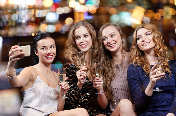women with champagne taking selfie at night club stock photo