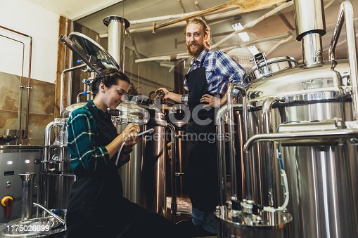 Women with clipboard working at brewery or beer plant. Brewery worker opening a lid of a beer cask t a craft beer brewery. Small business concept.
