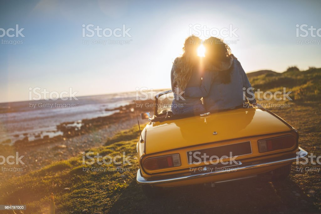 Women with convertible car relaxing at the beach at sunset royalty-free stock photo