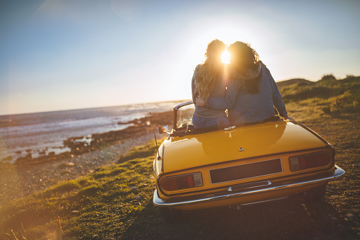 Women With Convertible Car Relaxing At The Beach At Sunset Stock Photo - Download Image Now