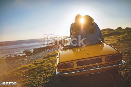 Women With Convertible Car Relaxing At The Beach At Sunset Stock Photo & More Pictures of 20-29 Years