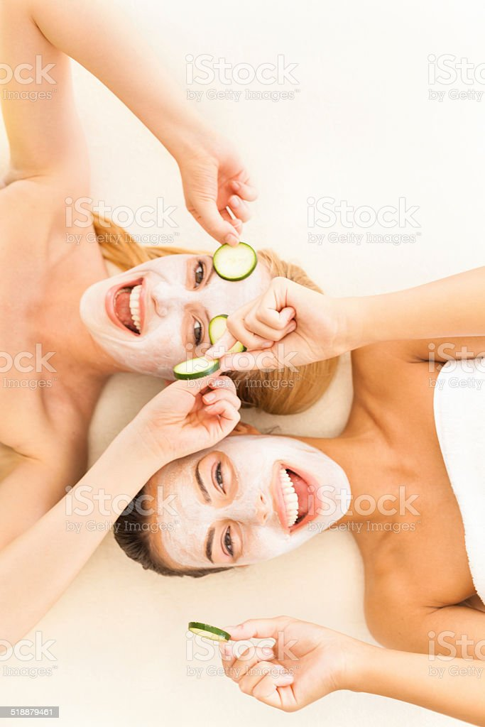 Women with cucumber slices on eyes and facial masks stock photo