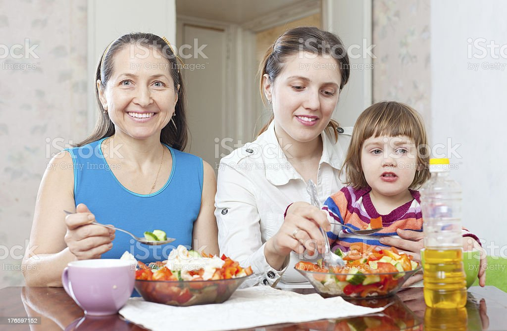 women with girl eats vegetables salad royalty-free stock photo