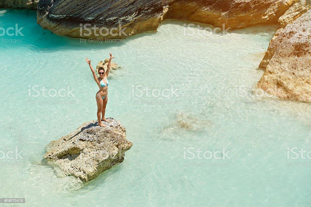 Women with hands up on beach – zdjęcie