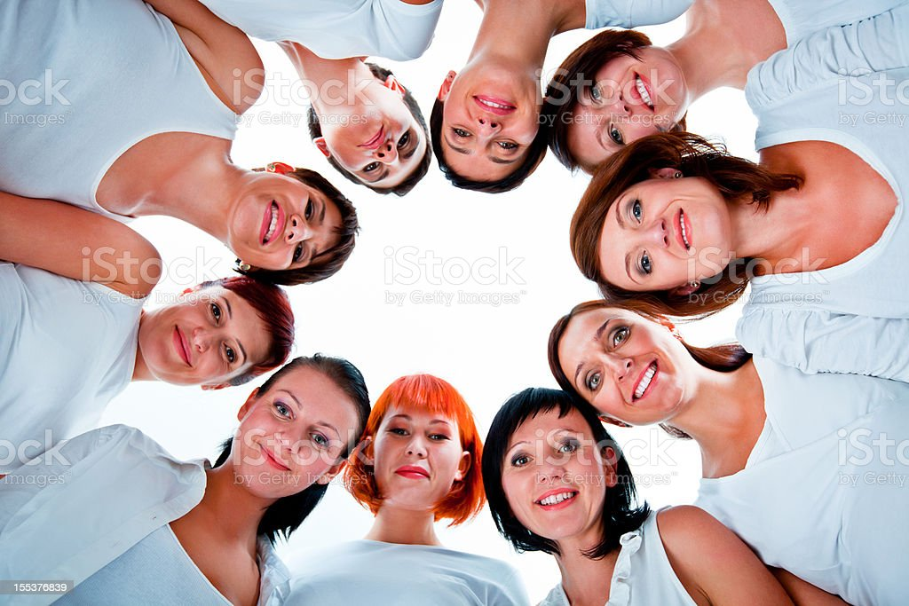 Women with heads together Group of women standing in the circle, smiling at the camera against white background. Low angle view. Adult Stock Photo