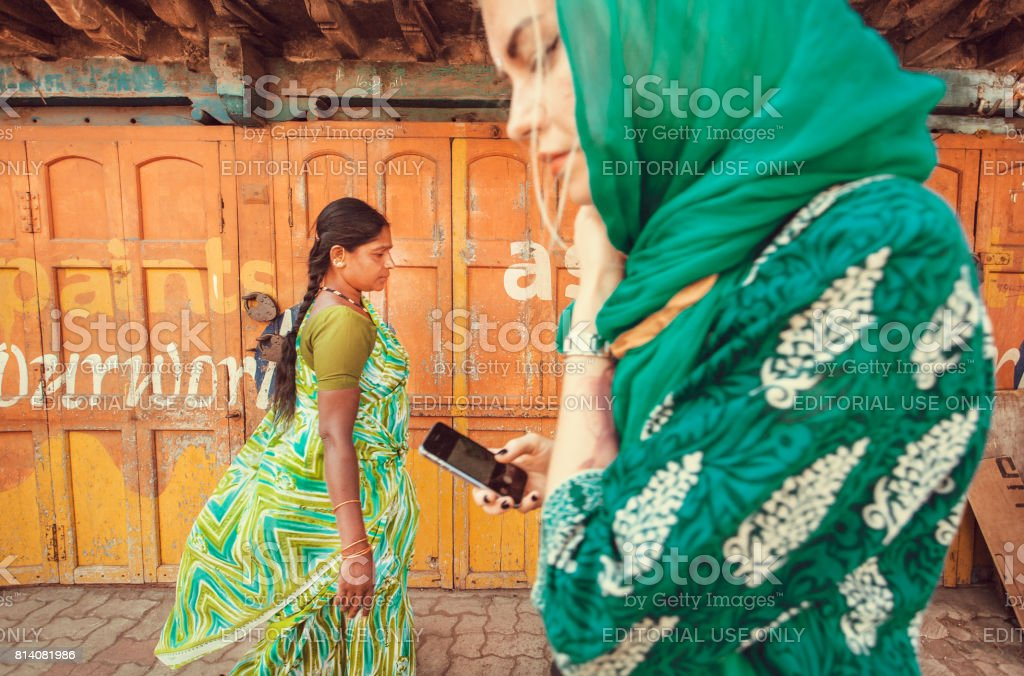 Women with mobile phones walking on street with colorful walls of houses stock photo