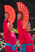 Rochester, England -  July 2018 : A group of women with red fans performing Tai Chi exercises during cultural and folklore festival