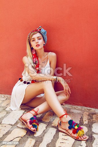Beautiful woman sitting on a stone street leaning against a red wall. In her beautiful long straight blonde hair is styled colorful scarf. Wearing nice white dress and colorful sandals.
