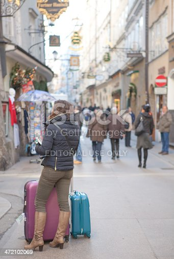 Salzburg, Austria - December 30, 2013: Salzburg - Dezember 30 .A women with suitcases is waiting in the Getreidegasse for a taxi wich drive her to the Airport..Dezember 30, 2013 in Salzburg,Austria.