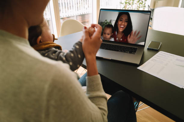 Women with their kids having a video call on laptop stock photo