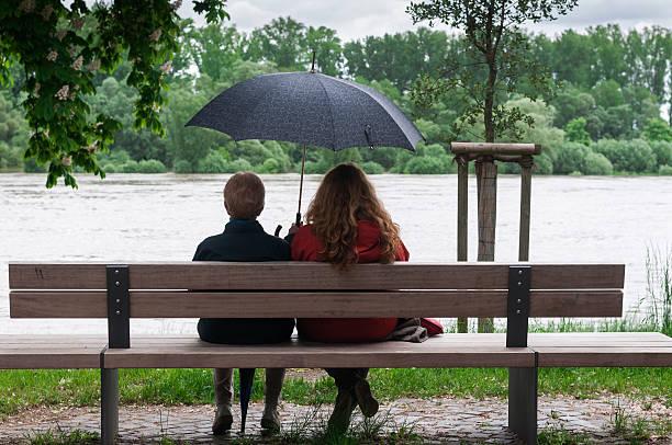 mulheres com guarda-chuva em um banco - banco assento - fotografias e filmes do acervo